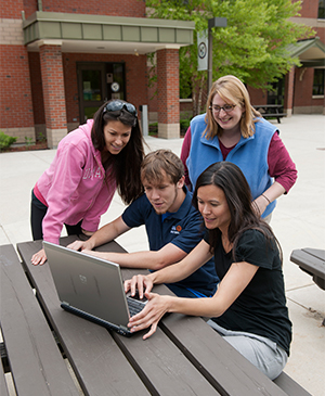 Group of students looking at laptop